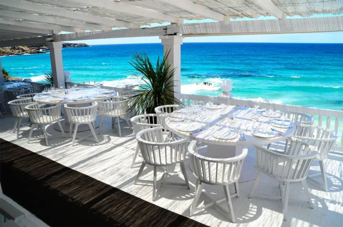 Blindingly Whitewashed Furnishings Contrast With The Technicolor Hues Of Gorgeous Beach Below At This Slick Beachside Restaurant Perched Atop Cliffs